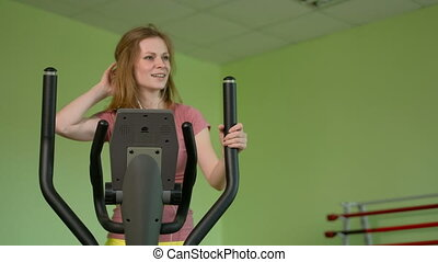 Young fit woman using an elliptic trainer in a fitness...