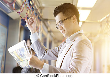 Taking public transport to work - Asian Chinese businessman...