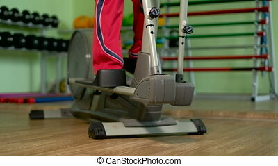 An elderly woman on an elliptical trainer in a gym 4k