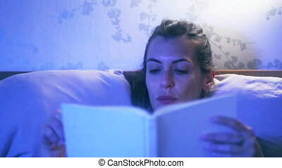 Frontal shot of a woman in bed reading a book