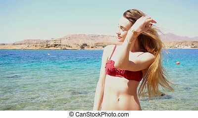 young woman in red swimsuit posing on the sea beach