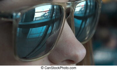 young pretty girl in sunglasses looks at the planes at the...