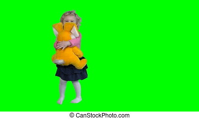 Cute little girl dancing with her big best friend bunny isolated on green