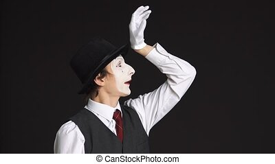 man MIME with a sour face on black background.