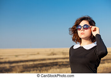 photo of beautiful young girl in sunglasses standing in the field