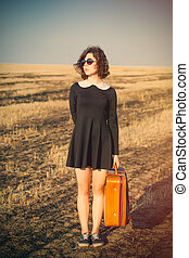 photo of beautiful young girl standing with suitcase in the field
