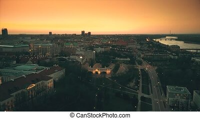 Aerial shot of Vistula river and Warsaw buildings in the evening, Poland. Orange sunset sky.