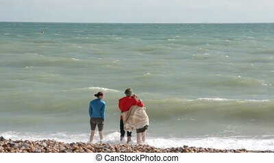 UK, Brighton. Young couple and friend are on the shore of Atlantic ocean. A couple is hugging, a girl is standing side by side. The seagulls are walking on the foreground.