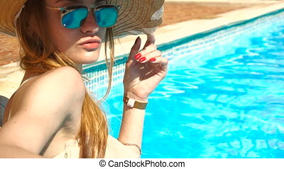 girl in straw hat and sunglasses sunbathing and swimming in the pool