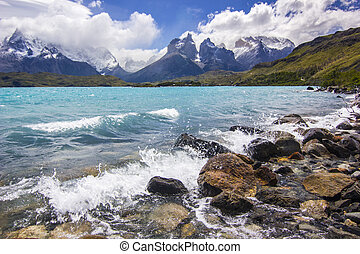 mountains of patagonia in haze at daylight with shore of blue lake