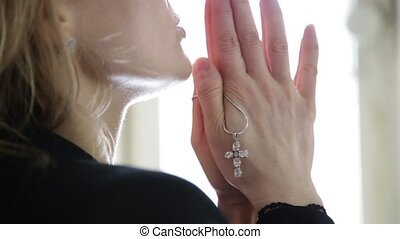 young woman is praying. close-up female hands holding chain...