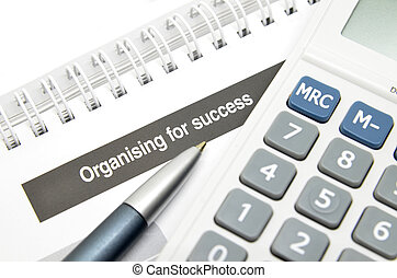 Organising for success printed on book with pen and...