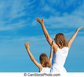 Woman and child with hands raised in the sky.
