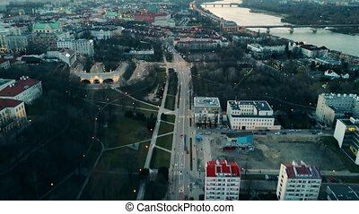 Aerial of Vistula river and Warsaw buildings and driving red...