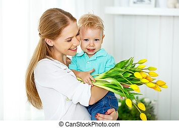 Happy mother's day. Baby son gives flowers for mom - Happy...