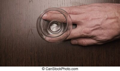 A glass of brandy male hand puts on the table. top view - A...