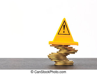 Risky coin stack and Warning label on white background.Financial crisis concept.