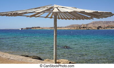 view of the blue sea and beach umbrella close-up
