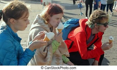 UK, Brighton. Three young friends on summer vacation enjoying ice cream in cones at the oceanfront. Teenage hipster friends have a rest.