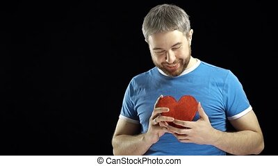 Smiling bearded man in blue tshirt holds two red heart...