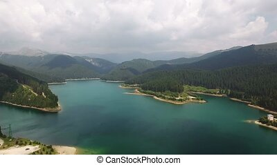 Panoramic aerial view of a lake among the forests and mountains