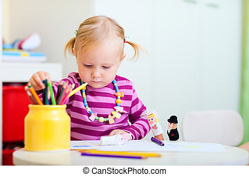 Toddler girl coloring with pencils