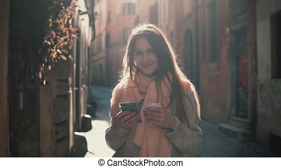 Young smiling woman walking in city at morning and using smartphone. Girl browse the Internet, texting with someone.