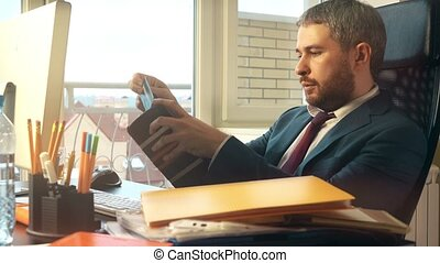 Handsome bearded businessman making online payment with his...