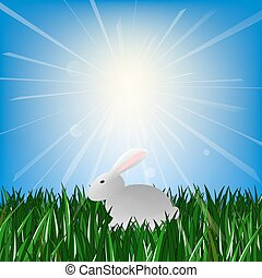 Easter Bunny sitting on green grass in the rays of the bright sun