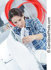 female repairman working hard on ventilation system