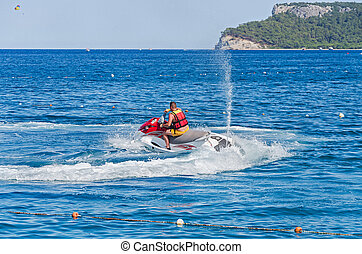 Jet skiing at sea on a sunny day.