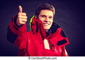 Cheerful man with weatherproof gear. Young male making...