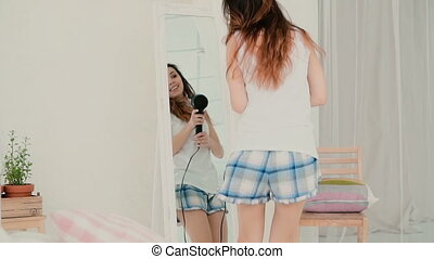 Young woman singing, using hairdryer as microphone. Girl dancing in pajamas in front of mirror. Slow motion.