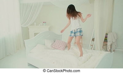 Happy young woman wearing pajamas jumping on her bed. Brunette girl feeling happy in the morning. Slow motion.