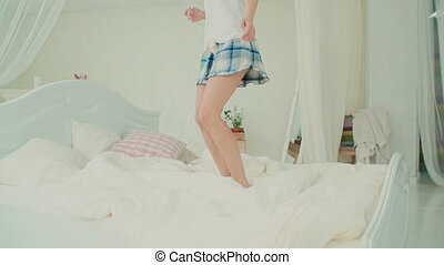 Close-up view of happy young woman s leg wearing pajamas, jumping on her bed in morning. Slow motion.