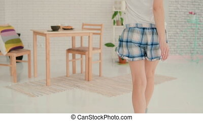 Funny young woman dancing in kitchen, running through the...