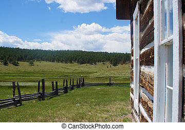 Side of Log Home - The side of a log home with a fence.