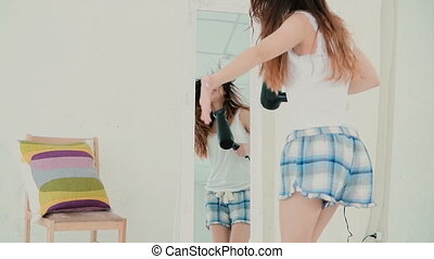 Young woman singing while using hairdryer. Girl in pajamas...