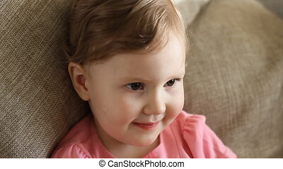 A little girl eats candy, smiling and looking at the camera