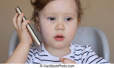 Baby girl talking on the phone, surprised and laughing.