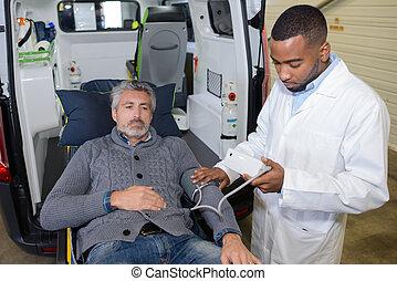 Paramedic taking patient's blood pressure