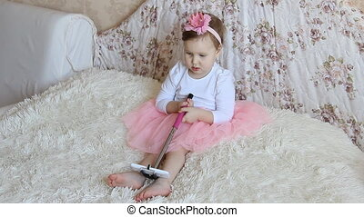 A little beautiful funny girl takes pictures of Selfie on the phone
