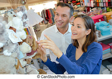 Couple looking at soft toys