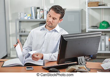 Office worker reading at his desk