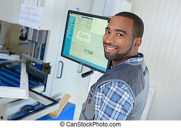 worker posing next to a screen