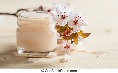 Moisturizing cream and cherry blooms on wooden background -...