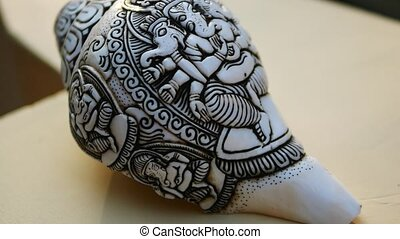 Seashell for music with Ganesh sculpture and palm trees -...