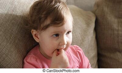 A little girl eats candy.