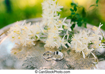 Wedding rings on the flowers of jasmine on a metallic silver...