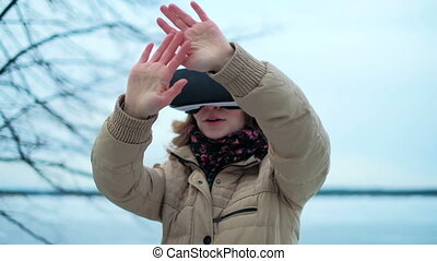 woman uses a virtual reality glasses on the street